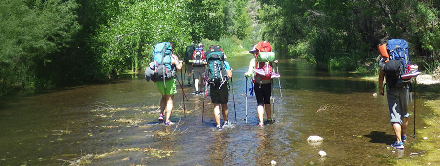 Mirasol of Mirasol clients with backpacks wading in a mountain stream